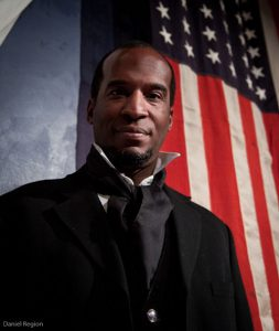 head shot of Phil Darius Wallace as Frederick Douglass. with the American Flag hanging behind him.